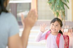 Student, der zur Schule und zum Zum Abschied winken geht Stockfotografie