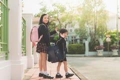 Student, der zur Schule und zum Zum Abschied winken geht Stockfotos