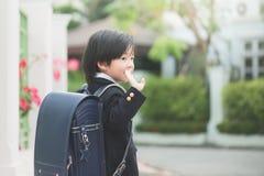 Student, der zur Schule und zum Zum Abschied winken geht Stockfoto