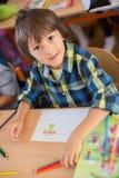 Student des ersten Grades der Junge, der am Schreibtisch an seinem ersten Tag an Sc sitzt Lizenzfreie Stockfotos