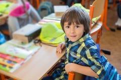 Student des ersten Grades der Junge, der am Schreibtisch an seinem ersten Tag an Sc sitzt Stockfoto