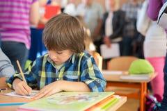 Student des ersten Grades der Junge, der am Schreibtisch an seinem ersten Tag an Sc sitzt Lizenzfreies Stockfoto