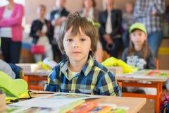 Student des ersten Grades der Junge, der am Schreibtisch an seinem ersten Tag an Sc sitzt Lizenzfreies Stockbild