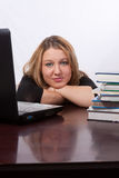 Student at desk. Attractive blond young caucasian woman sitting at desk in front of laptop computer beside a pile of text books stock images
