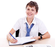 Student at desk. Young teen  sitting at desk with homework and smiling isolated on white background Stock Images