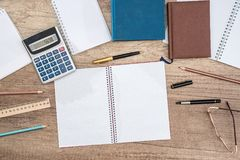 Student desk, calculator, pen, blank writing book, glasses. Student desk, calculator, pen, blank writing book, glasses Royalty Free Stock Image