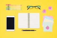 Student desk flat lay. Top view of working space table with open notepad, smartphone and office supplies. royalty free stock photo