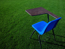 Student Desk on Football Field. A blue student desk sitting in the middle of the football field at a high school Stock Image
