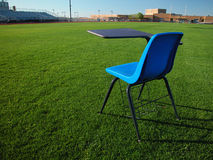 Student Desk on Football Field at School. A blue student desk sitting in the middle of the football field at a high school Stock Photo