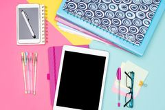 Student Desk Working Space Flat Lay. Top view photo of workspace with mock up tablet, folders and smartphone on pastel background. Student Desk Working Space royalty free stock images