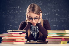 Student with desperate expression looking at her books Royalty Free Stock Photos