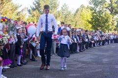 Student die ältere Klasse und das Mädchen ein Erstsortierer mit einer Glocke in ihrer Hand in der Schule der ernste Machthaber am Lizenzfreies Stockfoto