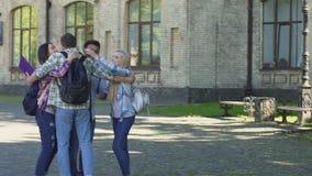 Student die aan beste vrienden lopen die hem wachten dichtbij universiteit, studenten het koesteren stock videobeelden