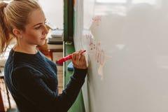 Student die aan boord tijdens wiskundeklasse schrijven royalty-vrije stock fotografie
