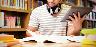 Student die in bibliotheek met tablet bestuderen Stock Afbeeldingen