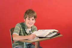 Student die bij bureau glimlacht Stock Foto
