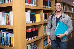 Student die bij camera in bibliotheek glimlachen Stock Afbeeldingen