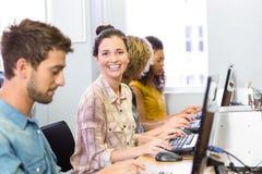 Student die bij camera in computerklasse glimlachen Royalty-vrije Stock Afbeelding