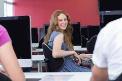 Student die bij camera in computerklasse glimlachen Royalty-vrije Stock Foto