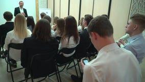 Student die de tekst voor het werk schrijven die smartphone binnen in het publiek gebruiken Mening van erachter van een groep stu stock videobeelden