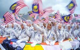 Student die de vlag van Maleisië golven die ook als Jalur Gemilang wordt bekend Stock Afbeeldingen