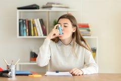Student die een astmainhaleertoestel thuis met behulp van stock afbeeldingen