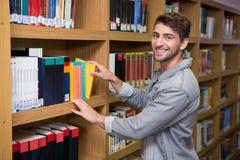 Student die een boek van plank in bibliotheek plukken Stock Fotografie