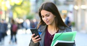 Student die en telefoon in de straat lopen controleren stock videobeelden
