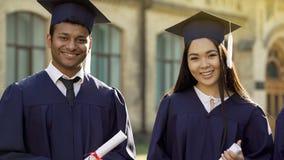 Student die in graduatieuitrusting met diploma's, onderwijs in het buitenland glimlachen royalty-vrije stock foto