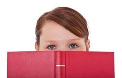 Student die haar gezicht achter boek verbergen Stock Afbeeldingen