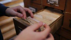 Student die het juiste boek in de oude de bibliotheekcatalogus van de stijlussr zoeken Sluit omhoog stock videobeelden