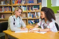 Student die hulp van privé-leraar in bibliotheek krijgen stock afbeelding