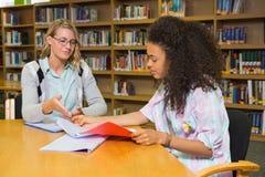 Student die hulp van privé-leraar in bibliotheek krijgen royalty-vrije stock afbeelding