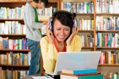 Frau in der Bibliothek mit Laptop Lizenzfreie Stockfotos