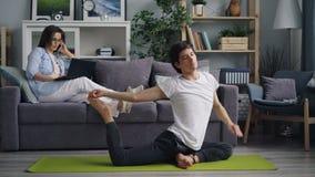 Student die laptop met behulp van die op mobiele telefoon spreken wanneer vriend het praktizeren yoga stock video
