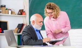 Student die leraar vragen over taak Opvoeder en leerling die boek bekijken Het verklaren van moeilijke informatie Het oplossen va stock foto's
