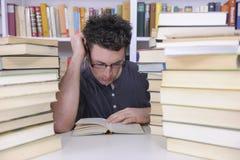 Student die met boeken in een bibliotheek onderzoekt royalty-vrije stock fotografie