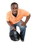 Student die met een zak knielt die omhoog glimlachend kijkt stock afbeeldingen
