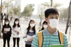 Student die mondmasker dragen tegen smog in stad royalty-vrije stock fotografie