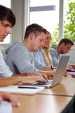 Student die nota's neemt bij laptop Stock Afbeeldingen