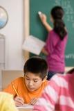 Student die in notitieboekje in schoolklaslokaal schrijft Stock Fotografie
