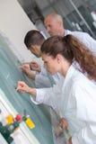 Student die op bordbord tijdens chemieklasse schrijven royalty-vrije stock foto