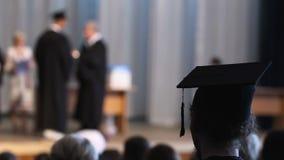 Student die op stadium graduatieceremonie bekijken, mensen die diploma's ontvangen stock videobeelden