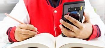 Student die slimme telefoon in klasse met behulp van royalty-vrije stock foto