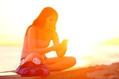 Student die smartphone met behulp van bij zonsondergang op het strand royalty-vrije stock afbeeldingen