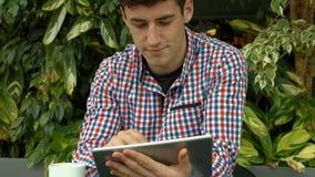 Student die tablet buiten op campus gebruiken stock footage