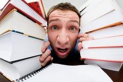 Student die tussen boeken wordt gedrukt Stock Afbeelding