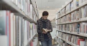 Student die zich op vloer in bibliotheek bevinden, die boek lezen Verticale vorm, zijaanzicht, midle schot stock video