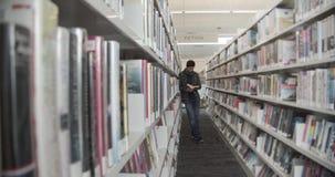 Student die zich op vloer in bibliotheek bevinden, die boek lezen Verticale vorm, zijaanzicht, volledige lengte, stock footage