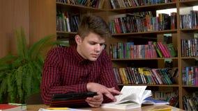 Student die zijn digitale tablet in een bibliotheek gebruiken stock video
